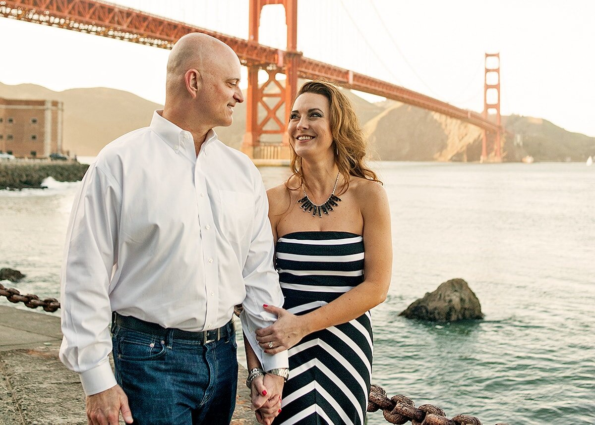 Couple walking at the base of the Golden Gate Bridge in San Francisco