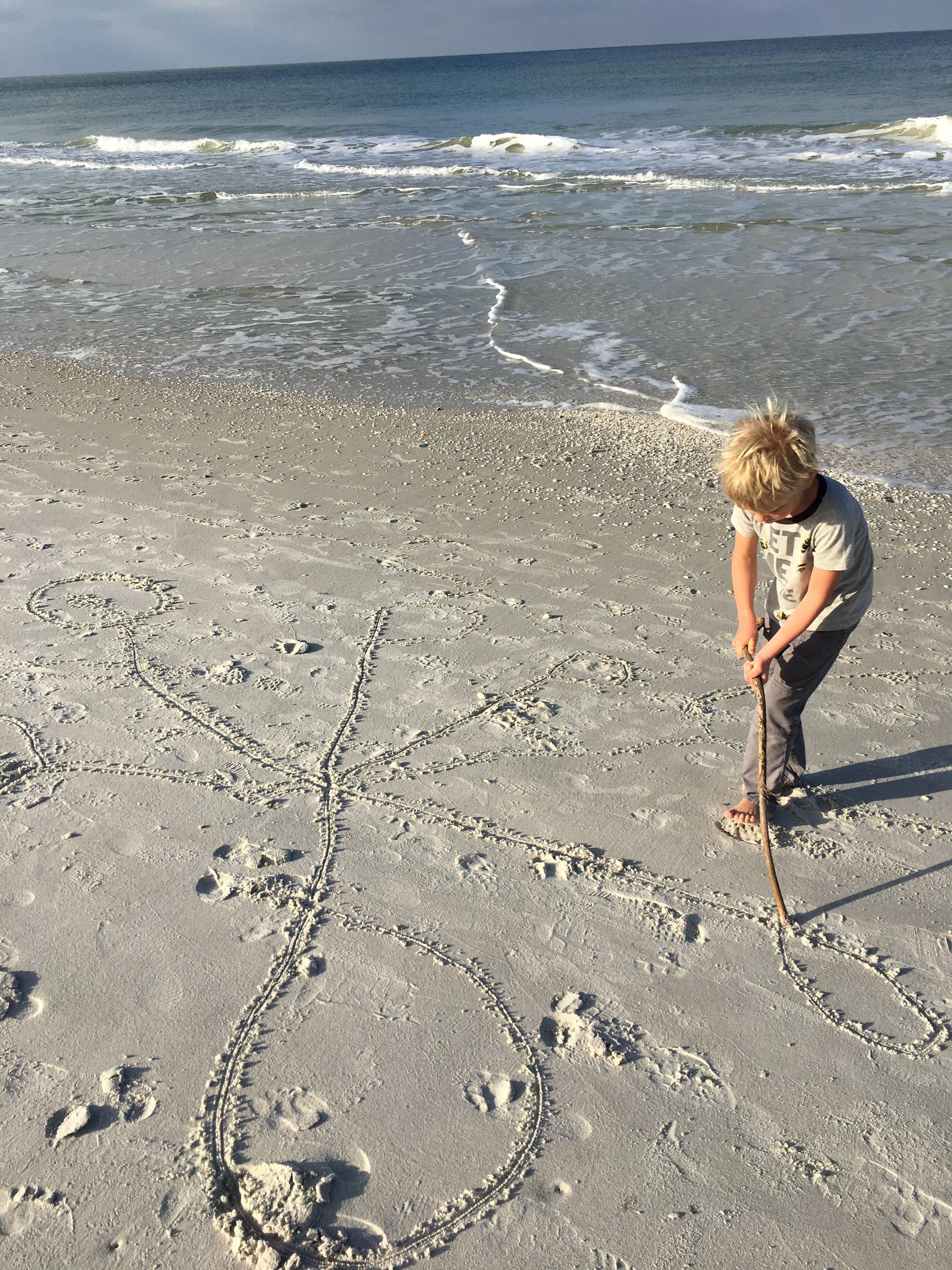 Joah noodling monster details in the sand.