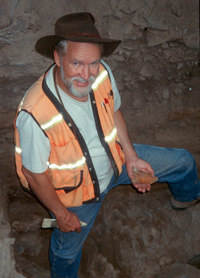 Dr. Jenkins at Paisley Cave with bison bone. Photo courtesy of Dennis Jenkins.