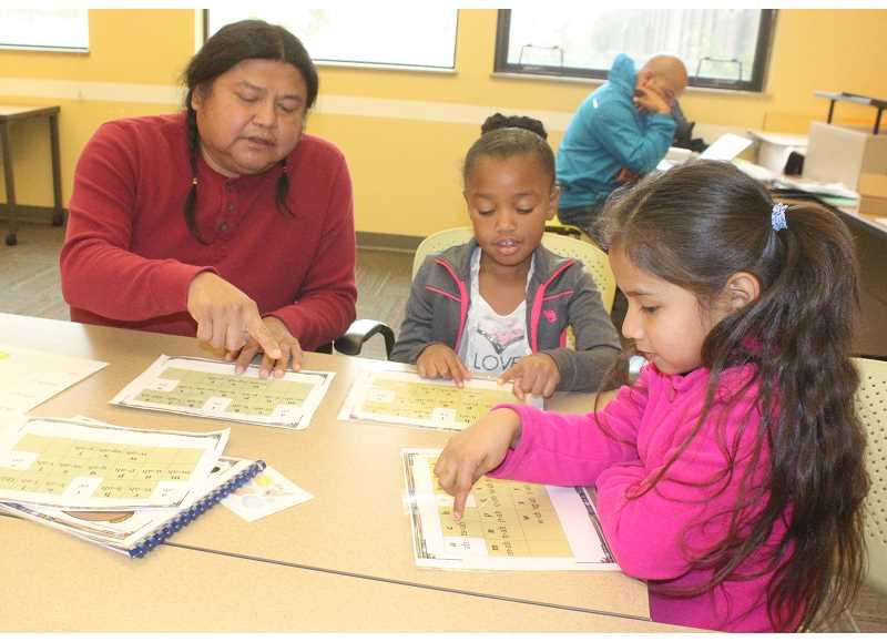 Dallas Winishut goes over Ishishklin (Wasco) alphabet with Warm Springs K-8 Academy first graders. Photo courtesy of the Portland Tribune.