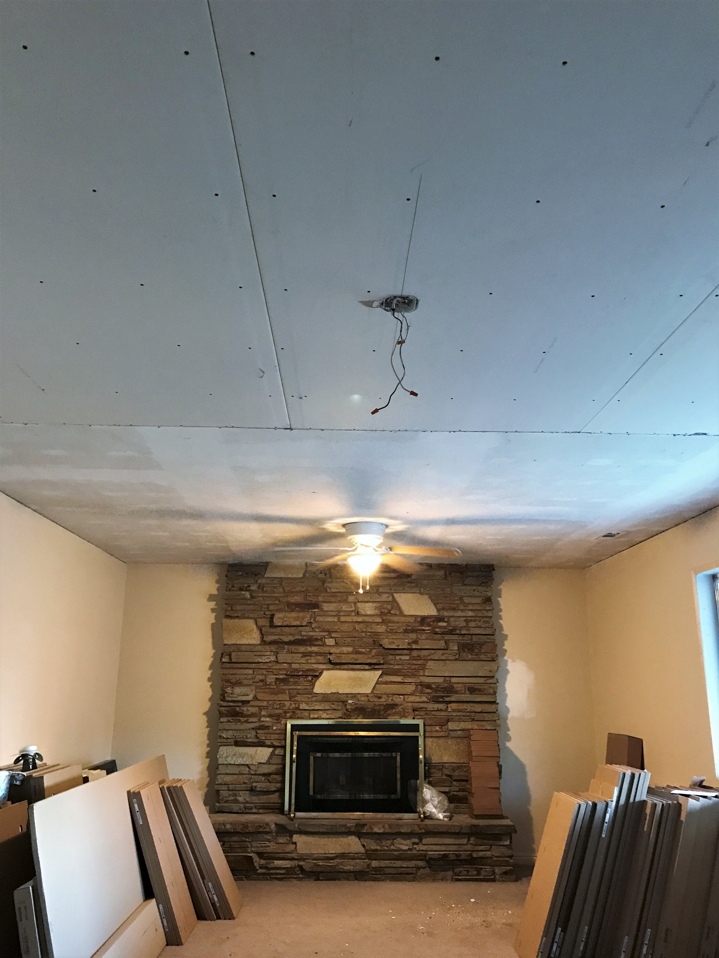 The ceiling is back in the den! Those boxes you see are all of our kitchen cabinets.