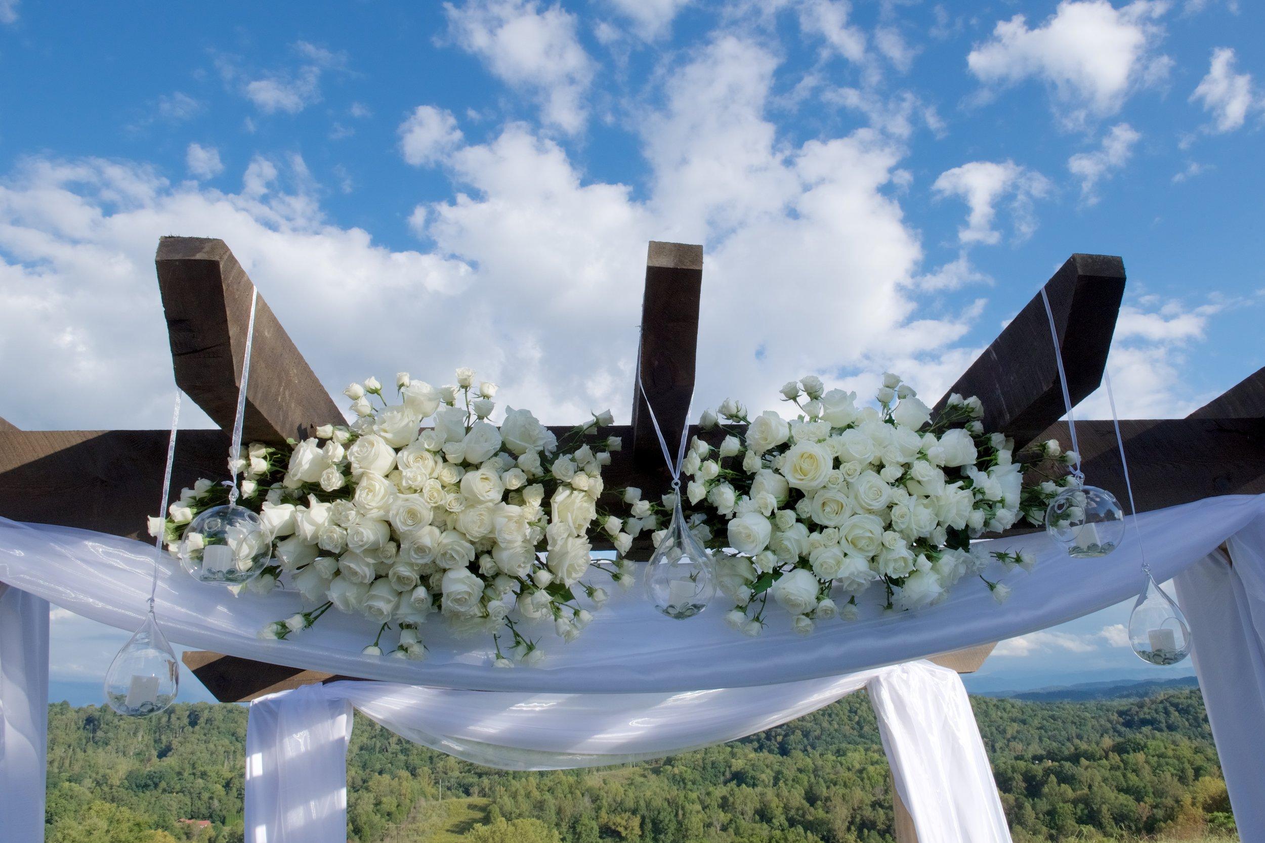 white roses on wedding arbor