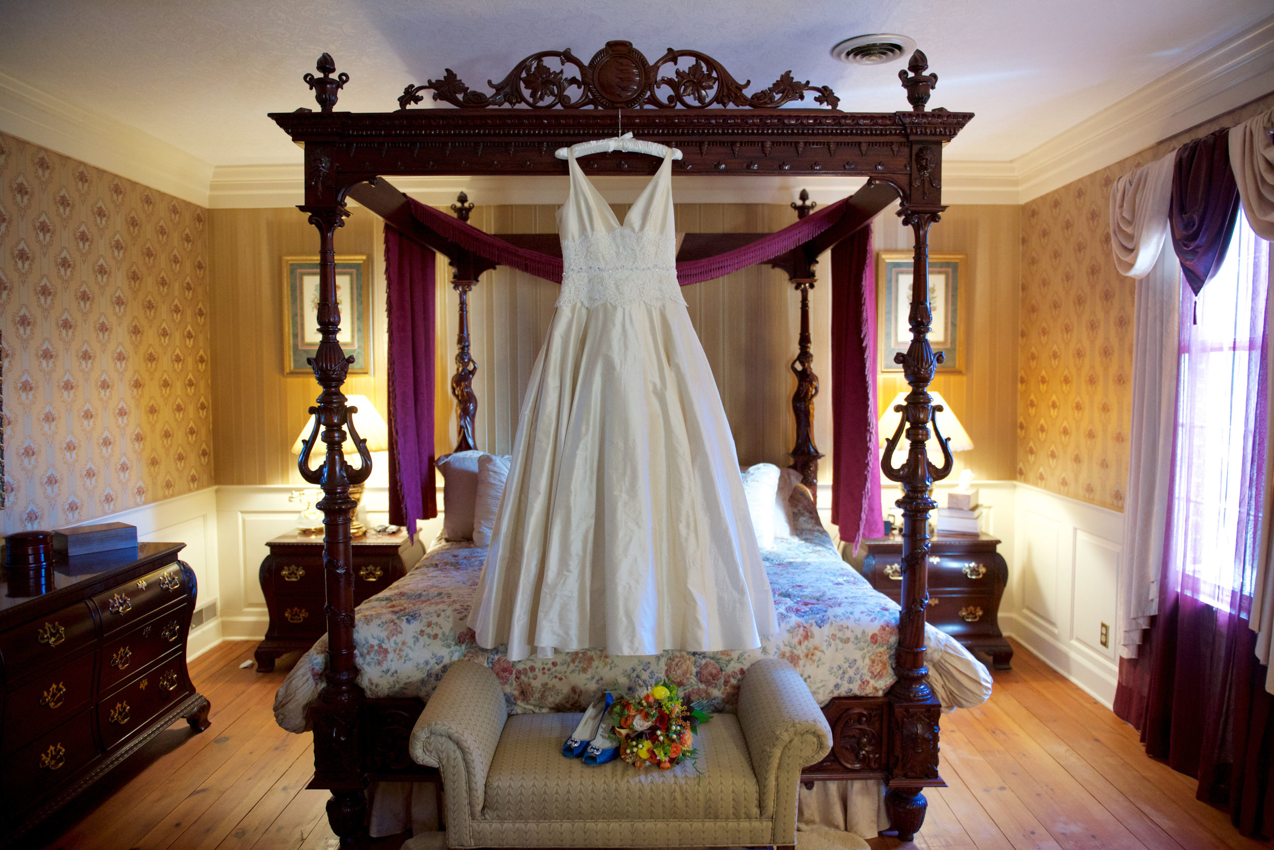 Wedding dress hung on canopy bed