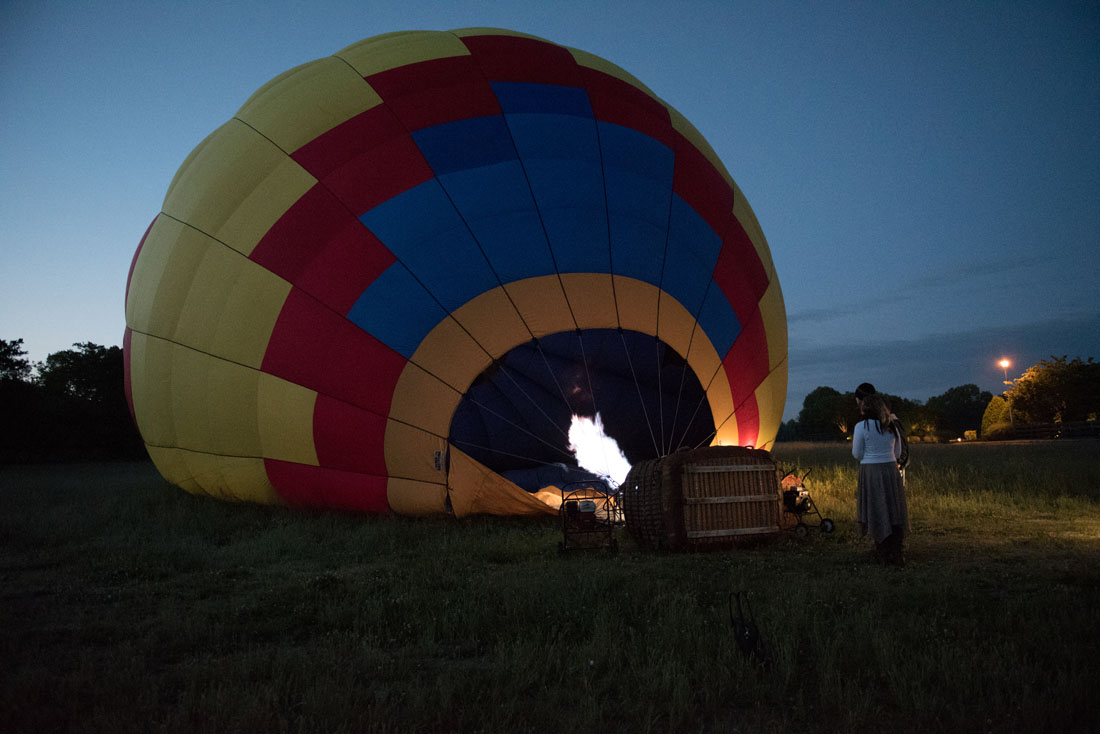 Bride & Groom wait as hot air balloon fills.