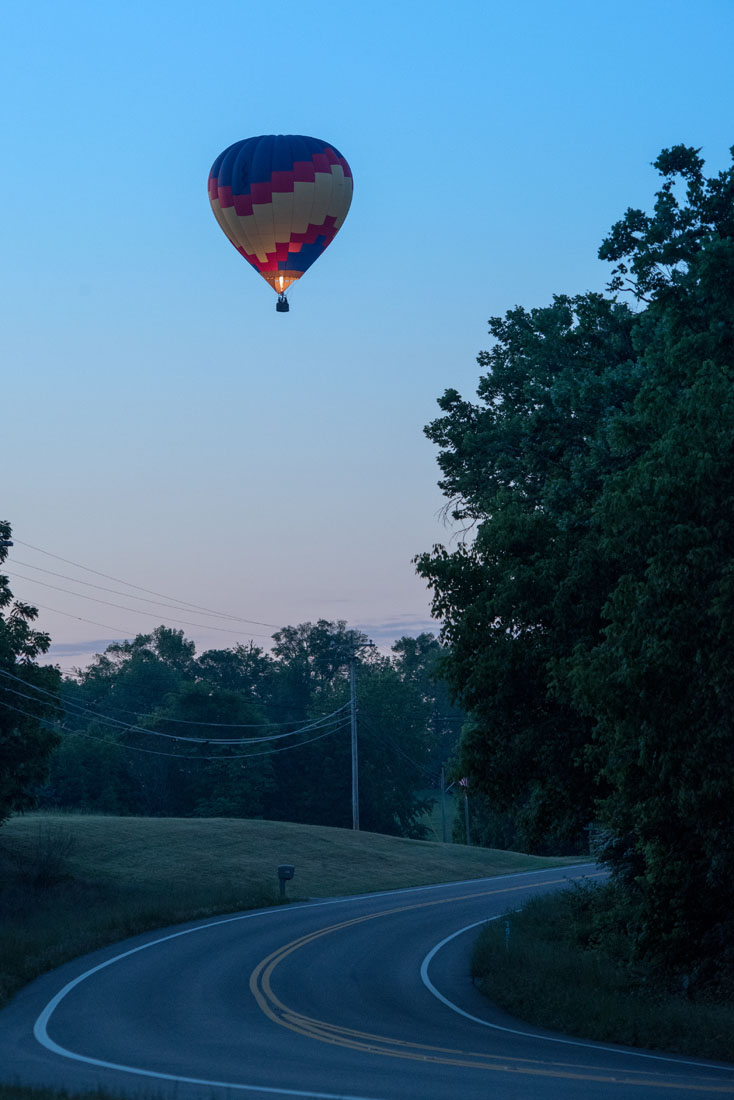 Bride & Groom light up early morning skies framed by trees in a hot air balloon!