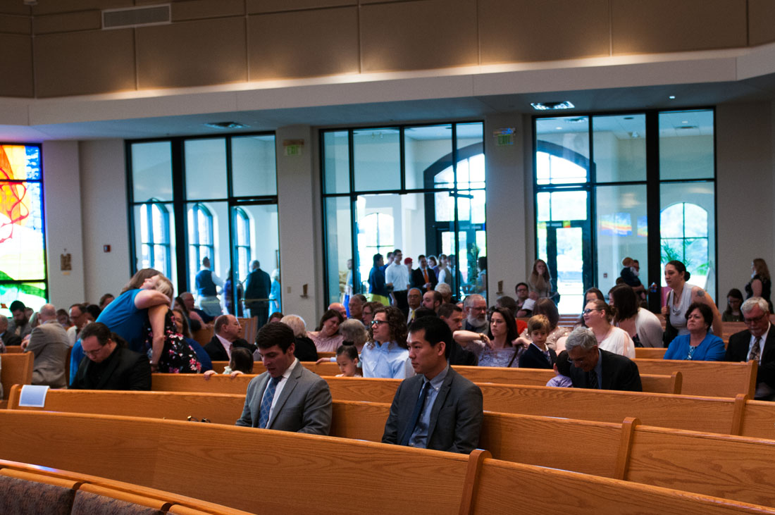 Wedding guests fill in the pews at the church.