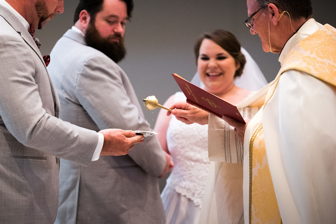 The wedding rings being blessed with Holy Water.