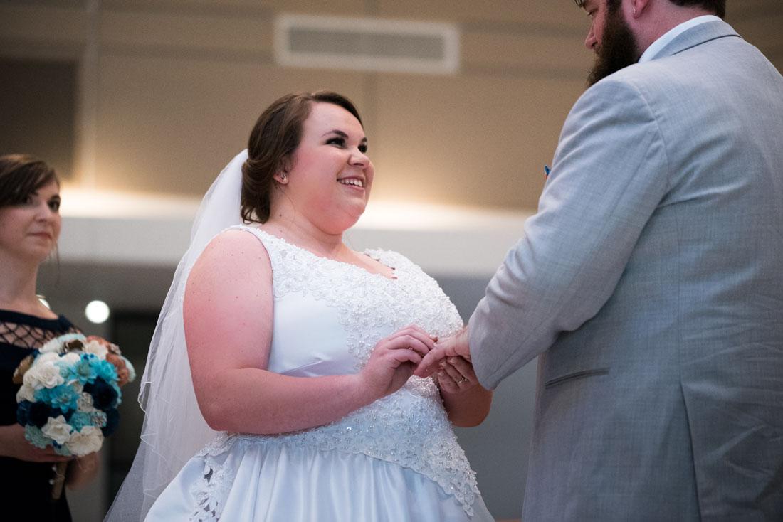 Ashley slips on the groom's ring.