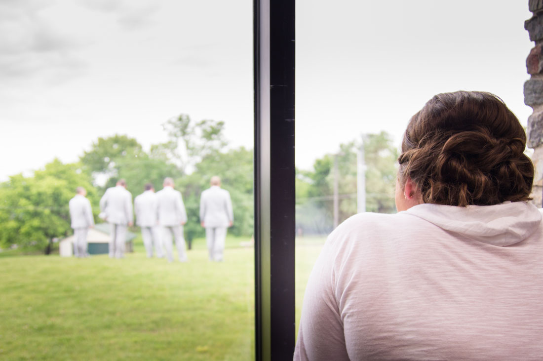 Ashley watches out a window as Paul & the groomsmen walks past.