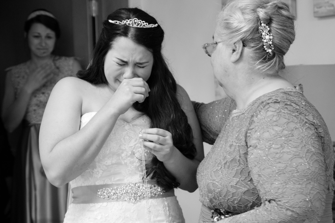Bride tears up as she receives locket with photo of her deceased father.