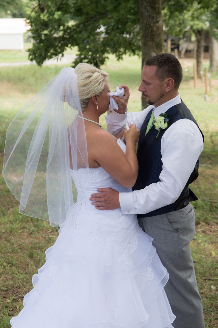 Groom wipes the tears of his bride. Such a tender moment.