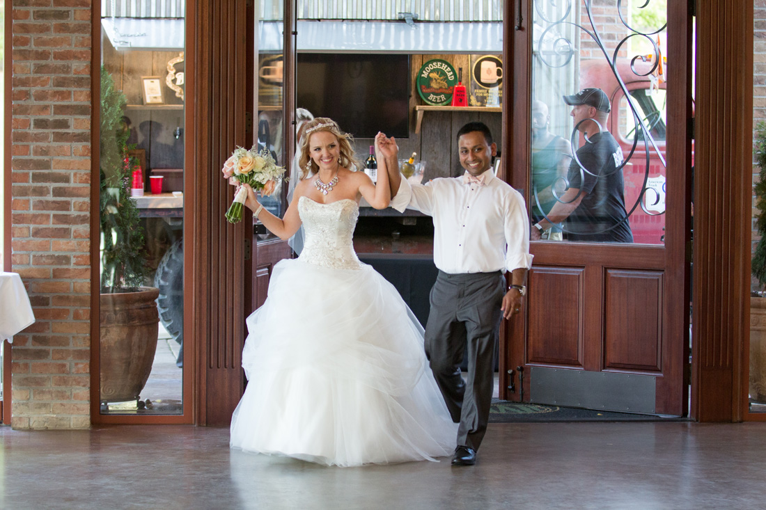 Bride & groom celebrate with hands held high as they enter the reception after being introduced