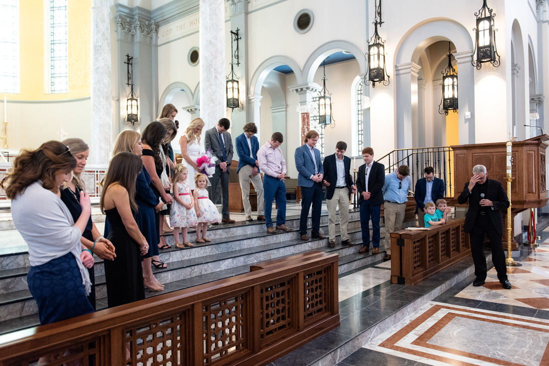 The wedding party bows their head in prayer during rehearsal.