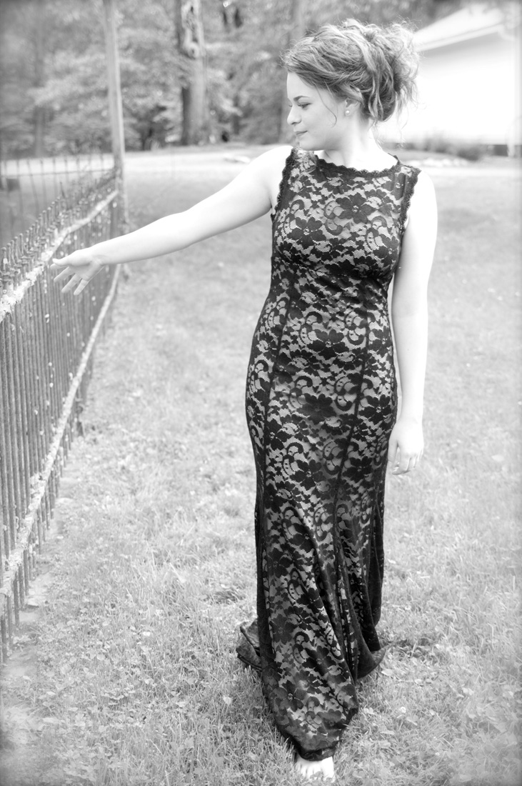 portrait of young lady walking along old fence line