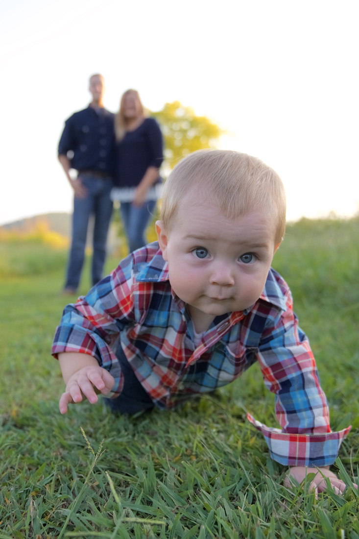 Family photo little boy crawling away from parents