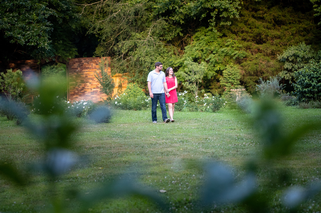 engaged couple strolls through a garden