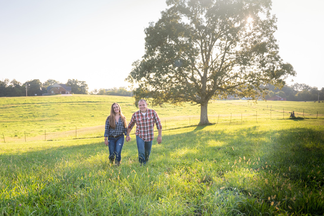 engagement photo of engaged couple walking thru a pasture
