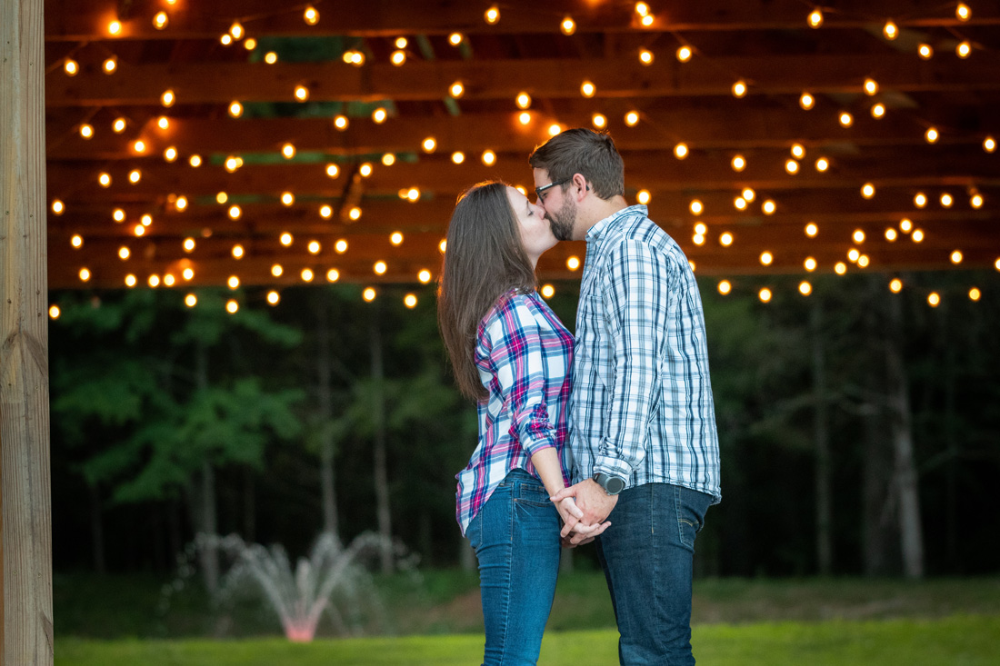 engaged couple under twinkling lights