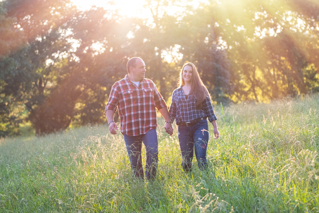 engagement photo of engaged couple with sunlight streaming all around