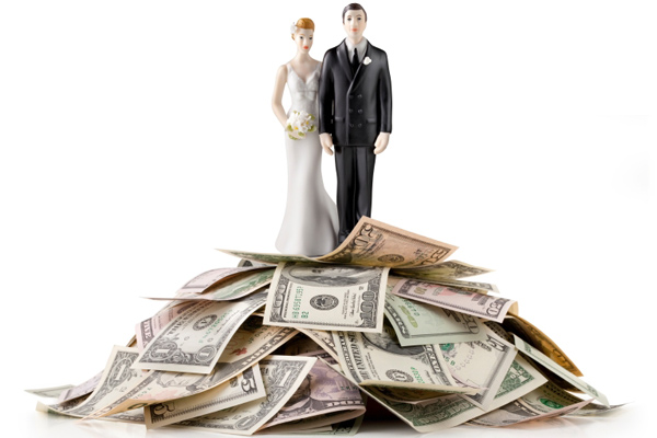 Bride & groom standing on a pile of cash