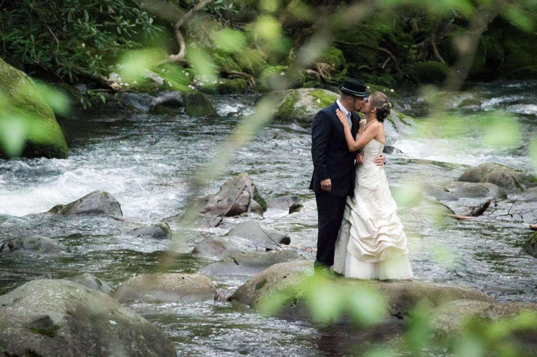 Bride and groom near a smoky mountain stream.