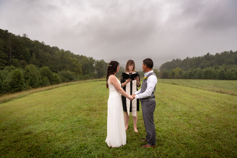Bride & groom in a Cade's Cove meadow beneath smoky mountains mist.