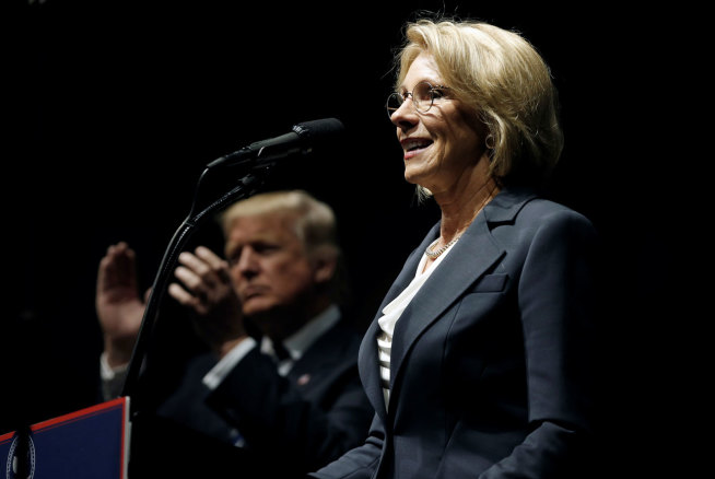 """Donald Trump applauds as Betsy DeVos speaks at Trump's """"Thank You USA"""" rally in Grand Rapids, December 9, 2016. 