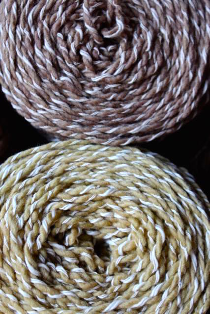 This wool yarn is wrapped with a cotton thread. Wool is a protein fiber and cotton is a cellulose fiber and they take dye differently as seen here. These yarns were dyed using a mordant and method for protein fiber.