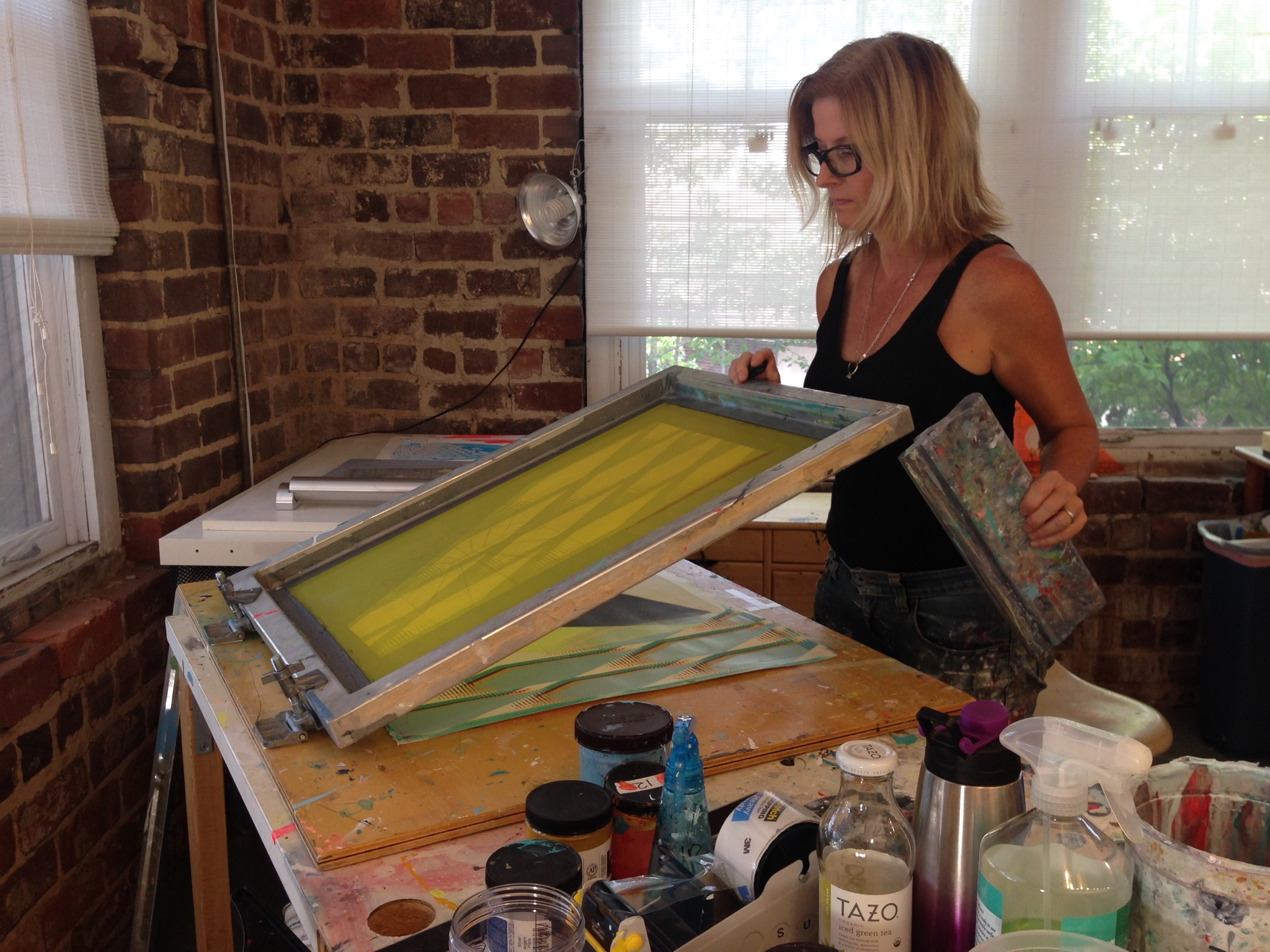 Stacie works with screenprinting equipment in her studio.