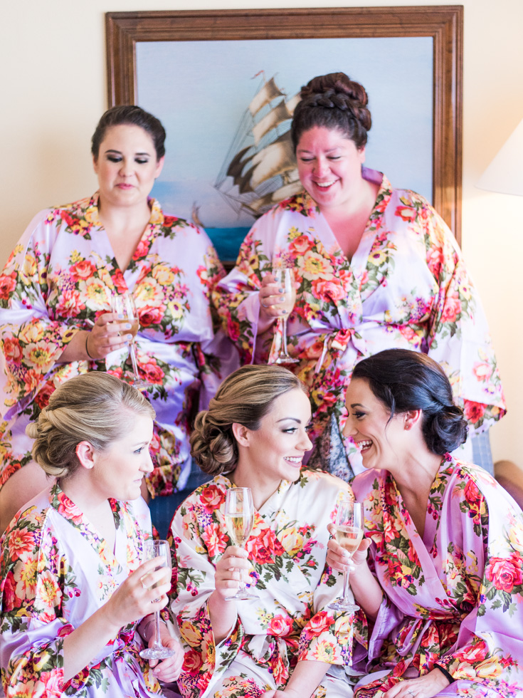 These beautiful bridesmaids are sipping champagne in their floral print getting ready robes in Mexico.