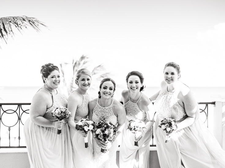 Sweet bridesmaids going in for a hug on their Caribbean balcony in Mexico.