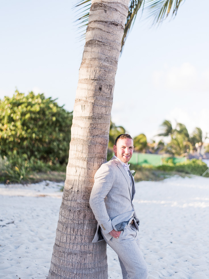 Beachy groom against a palm tree