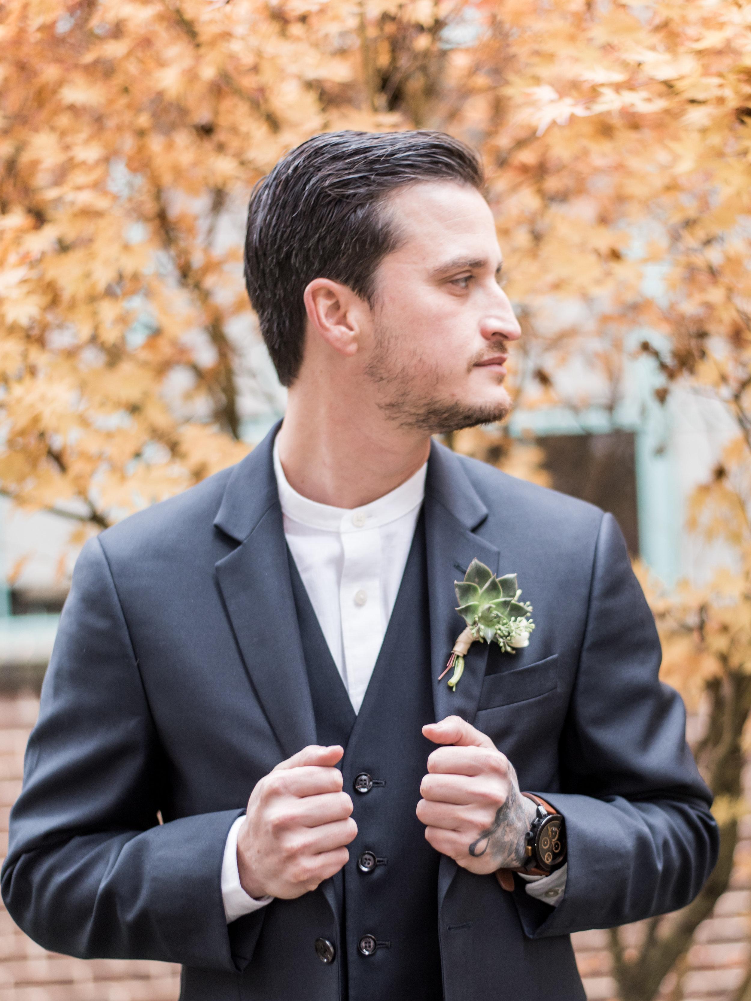 Handsome groom wearing grey suit