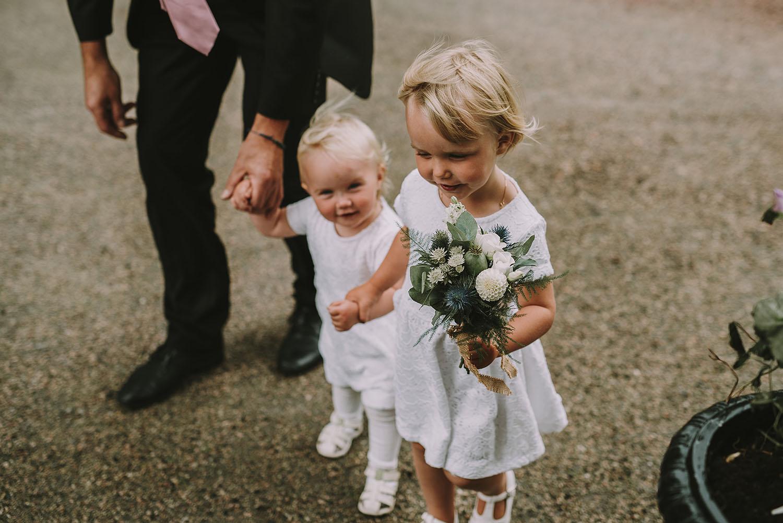 Barn i vita klänningar med blombukett