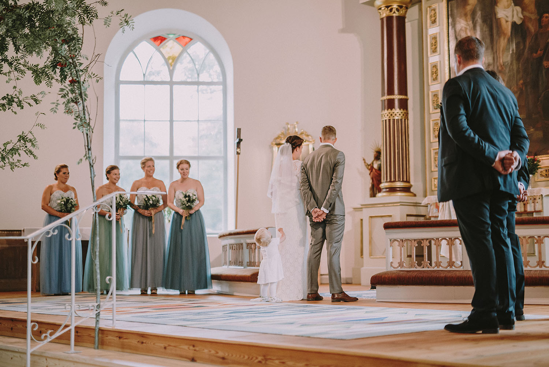 Brudnäbb går fram till brudparet framme vid altarringen i kyrkan