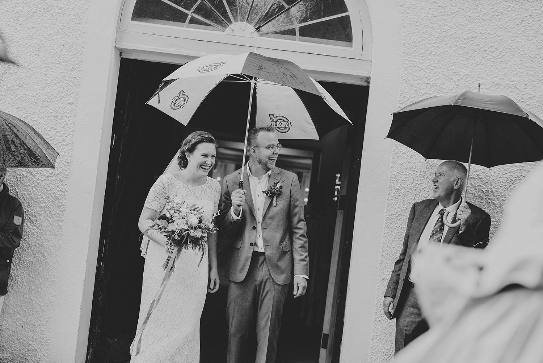 Brud i vit vintage spetsklänning och brudgum i grå kostym utanför kyrkan