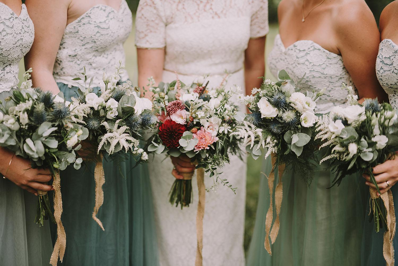 Bruden och tärnorna i sina klänningar med deras buketter i bohemisk stil
