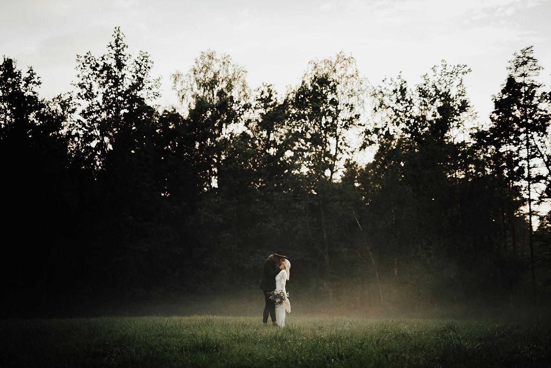 Brudpar på äng bland dimman en sommarkväll