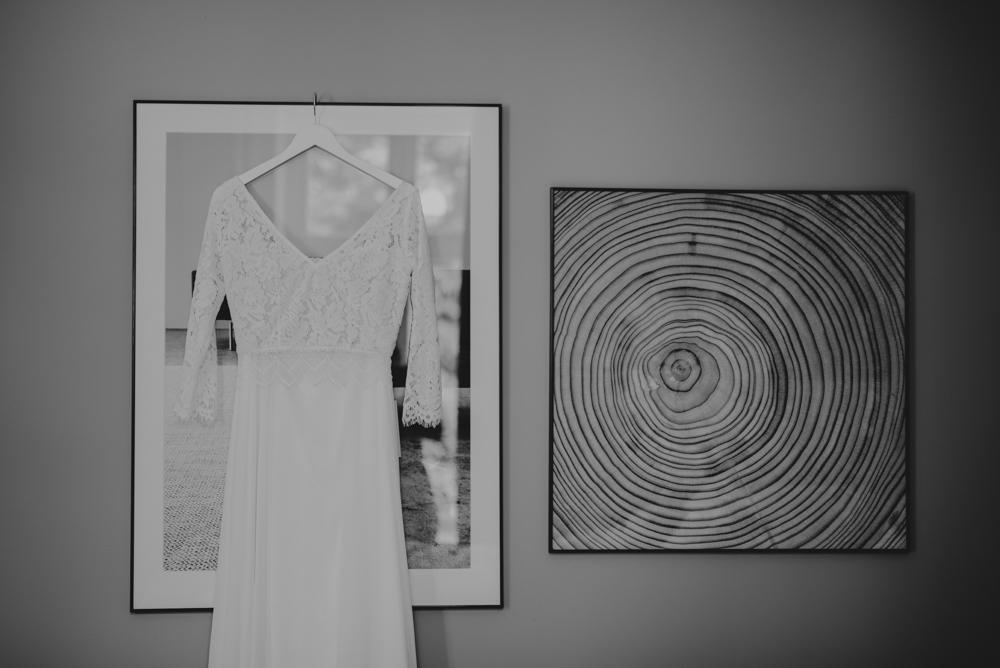 Brudklänning i spets hängandes i hotellrum under förberedelser innan bröllop i Malmö