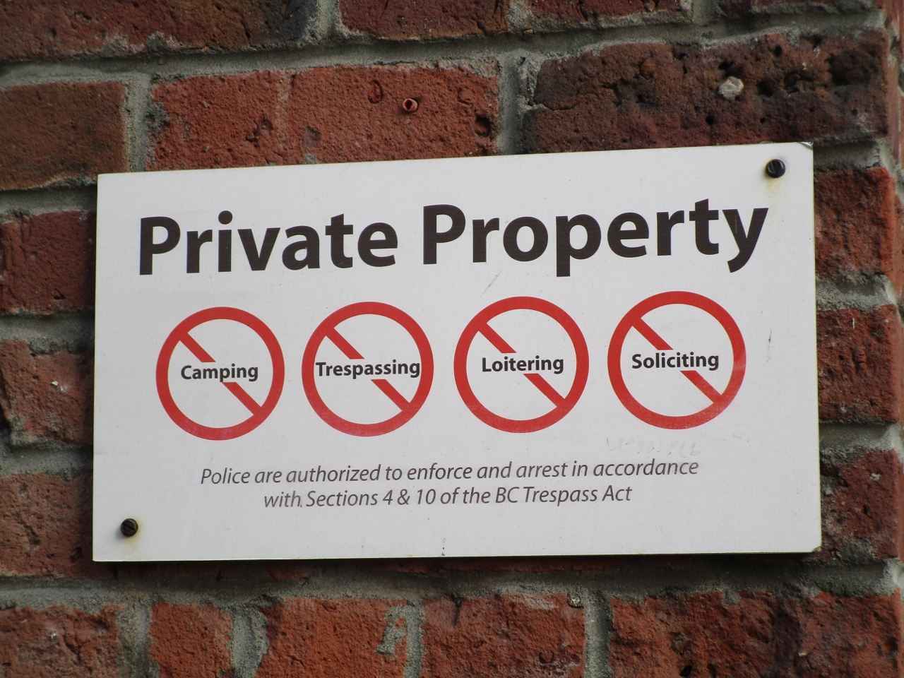 """""""Private Property. No camping, trespassing, loitering, or soliciting. Police are authorized to enforce and arrest in accordance with Sections 4 & 10 of the BC Trespass Act."""""""