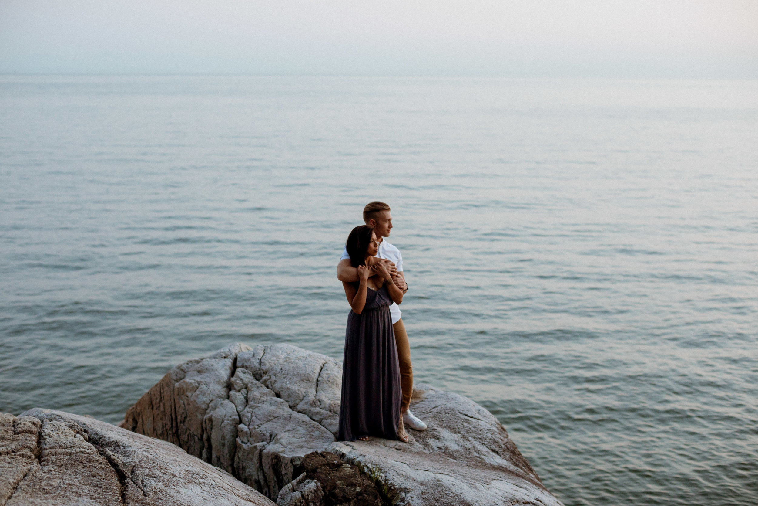 An intimate and romantic summer engagement session photo of a couple at Lighthouse Park in West Vancouver.