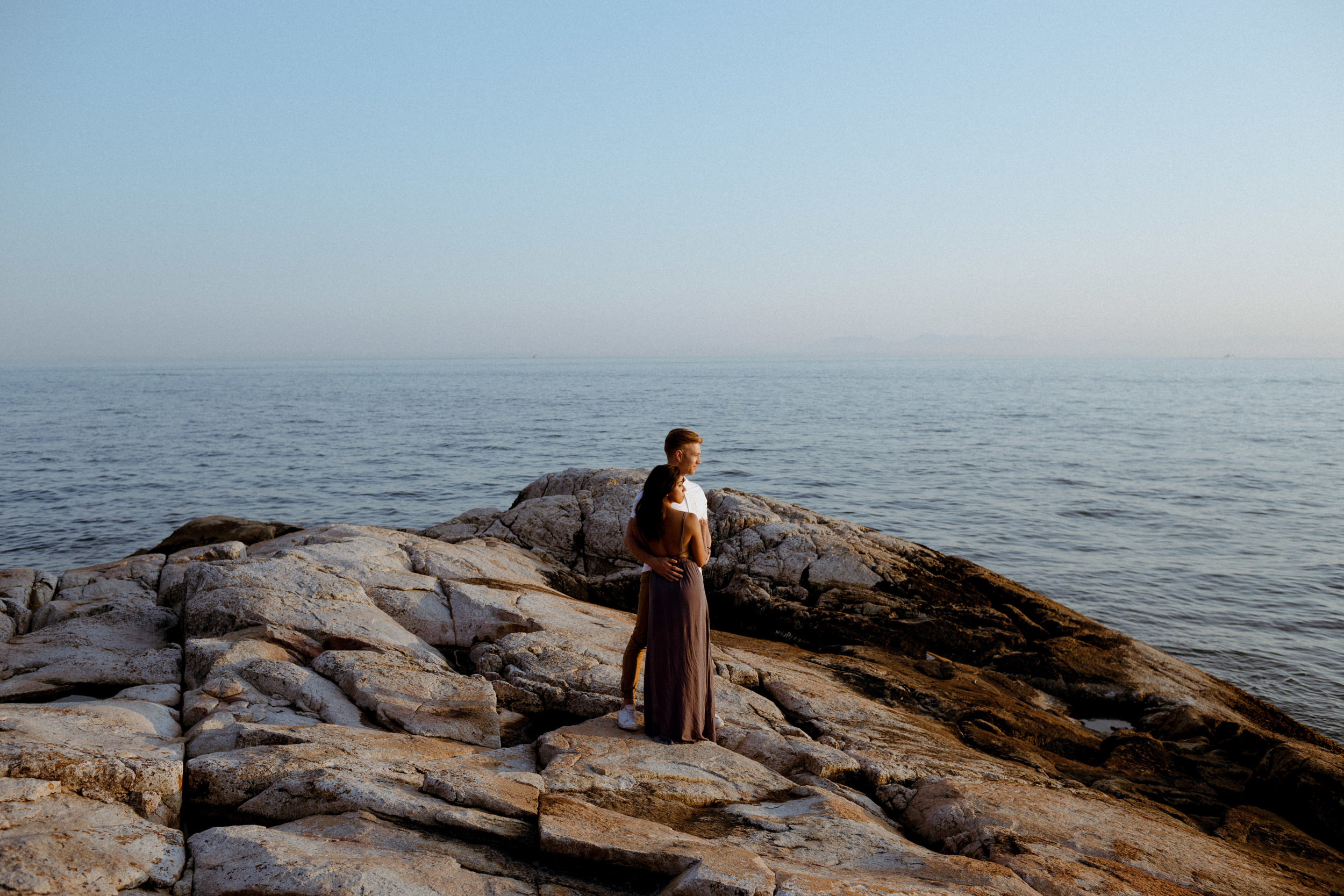 An intimate and romantic summer engagement session photo of a couple at Lighthouse Park in West Vancouver at sunset.