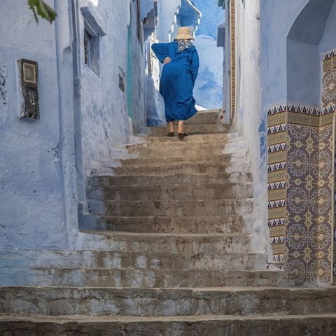 In Morocco's ancient blue city of Chefchaouen, there are stairs everywhere. Tiny narrow alleys are joined by steep staircases and wider thoroughfares have the occasional motorbike weaving (slowly) amongst the pedestrians. Here we captured a woman holding her back as she made her solitary way up some steps. Made us wonder at the millions of steps taken over a lifetime in this incredible place. #chefchaouen #morocco #moroccotravel #moroccolife #medina #market #peoplephotography #stocknotstock #SNSroadtrip #nikonphotography #peopleoftheworld #justgoshoot #travelgram #travelphotography  #streetphotography #cerulean #tonesofblue💙 #tonesofblue #womanofmorocco
