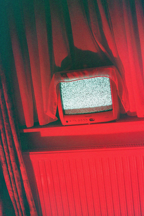 static tv in red tinted room (I do not own this image)