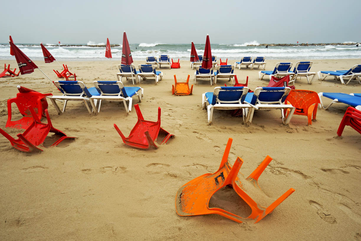 Tel Aviv beach after a storm, upturned plastic chairs on sand