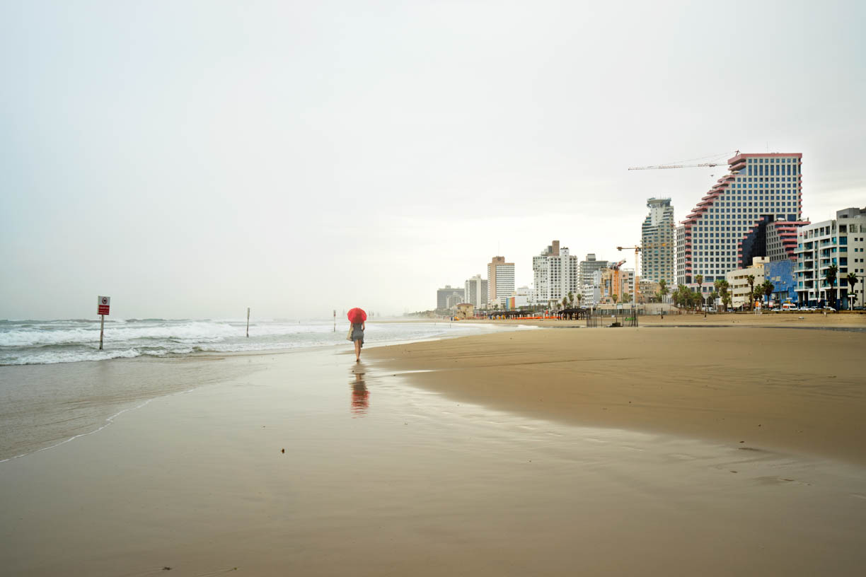 Tel Aviv beach, woman with a red umbrella walking on the sand