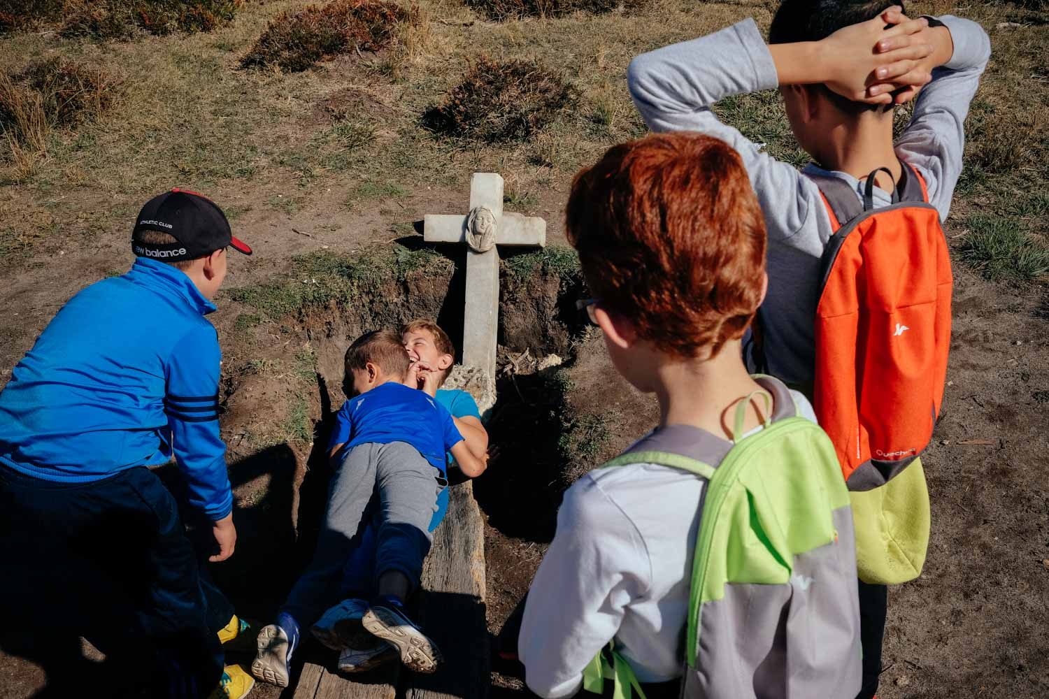 The kids from Peñaranda's Diego Marin school take turns throwing themselves into an open grave.