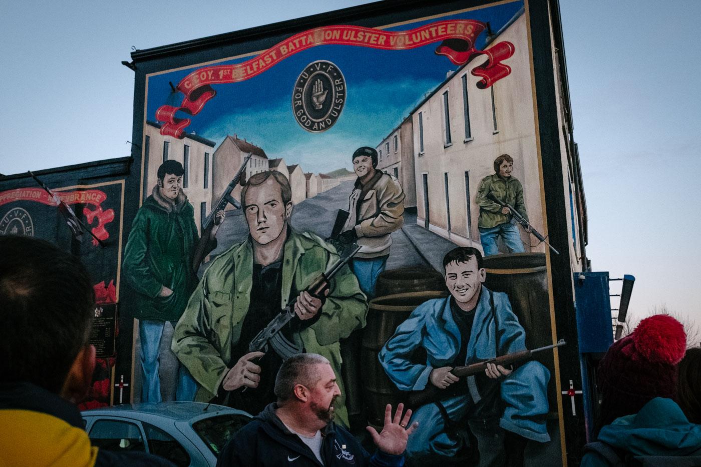 A mural of smiling loyalist paramilitaries on Shankill Road