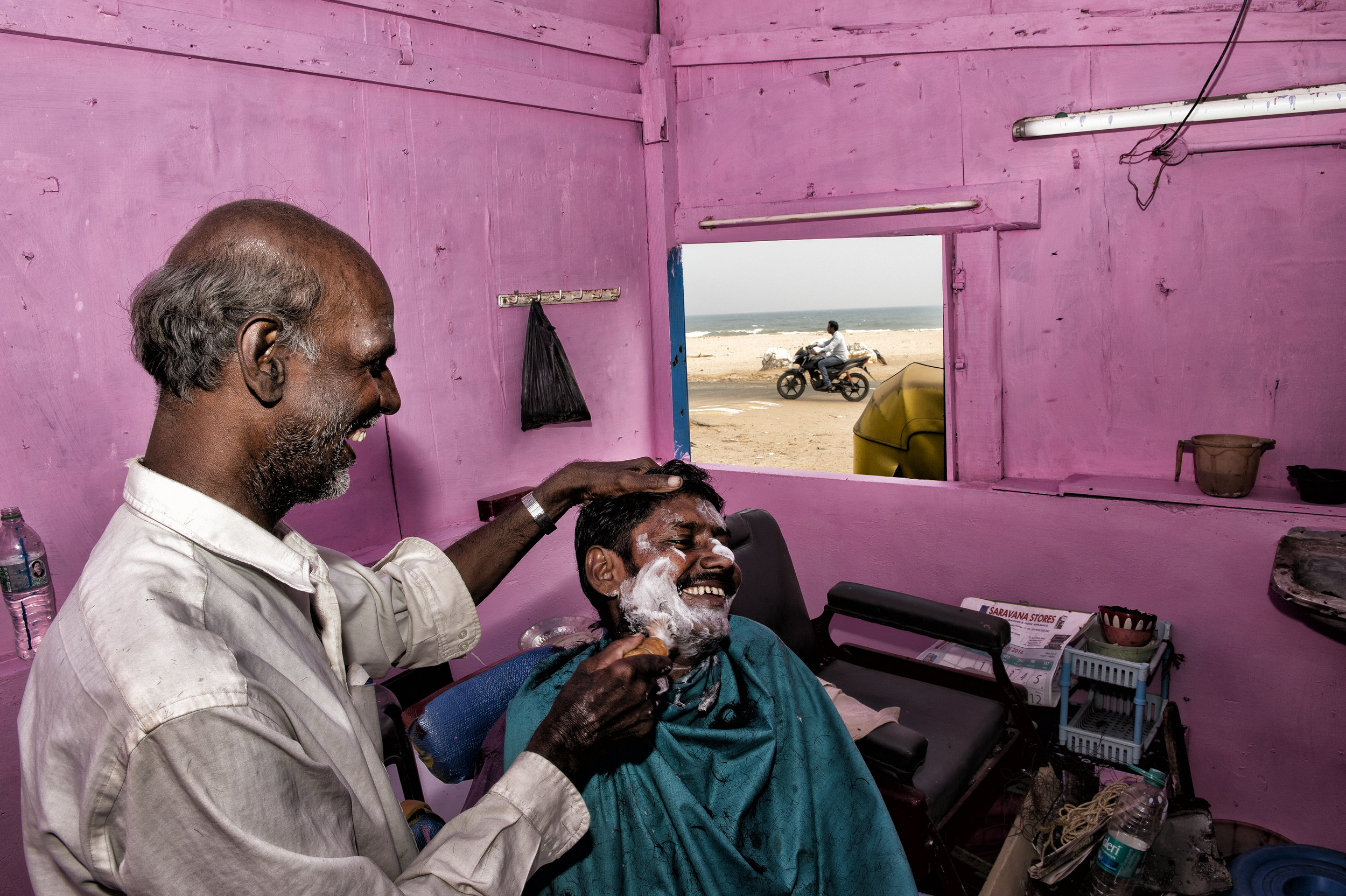 Hairdresser on the beach in India for National Geographic