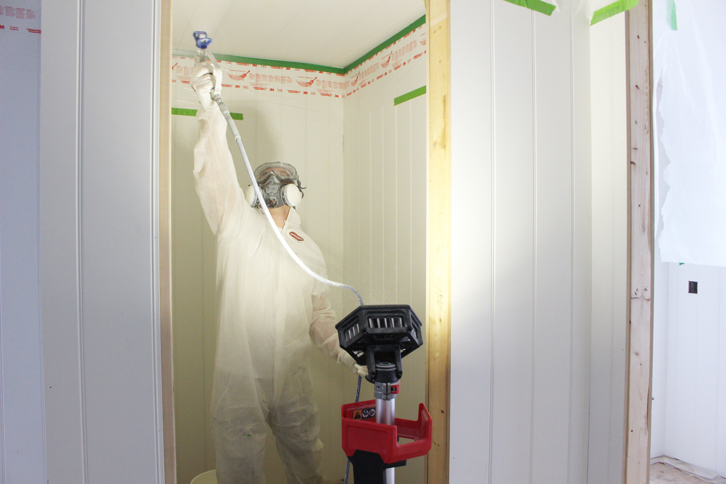 Spraying rough sawn spruce ceilings at a Lake Muskoka build using Simply White by Benjamin Moore Paints.